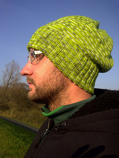 Man outside looking left and wearing glasses and a bright lime green slouchy knit hat with a wide ribbed brim.