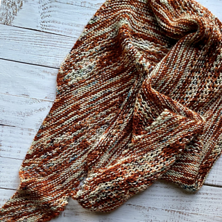 A rust, green, and cream colored shawl made up of garter stitch and mesh is heaped on white-washed boards.