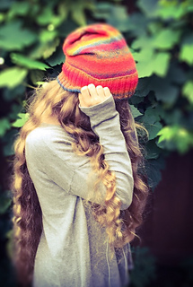 Woman with long blonde hair wearing a bright red slouchy knit hat with the ribbed brim folded up and her hand in front of her face.