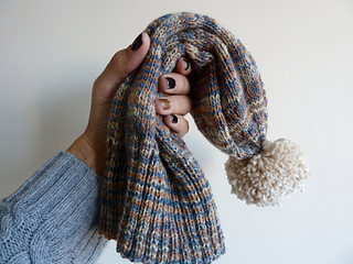 A hand holding a neutral coloured Sockhead hat with a beige pom pom.