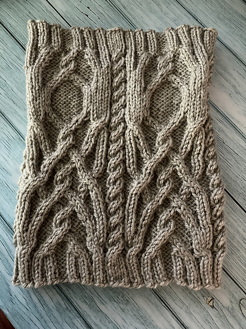 Test Knitters Wanted Cathedral Cable Cowl 2020, cowl is laid flat showing the cables on a teal washed plank background.