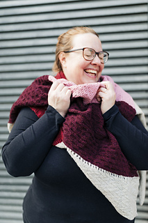 Lena snuggles up in Wayfarer, laughing at something our photographer said off camera. The texture of the stitch patterns plays beautifully with the different yarn colors.