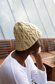 Side view of the hat with Charifa wearing it, showing that the cables flow out seamlessly from the brim.