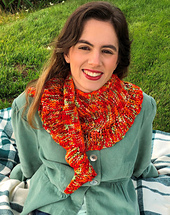 Model wearing cowl sized Ruffled Clear Sailing scarf in orange and mint variegated yarn