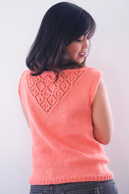 an asian woman with shoulder length dark brown hair with her back to the camera. She looks down over her back. She's wearing a coral-colored hand knit tank top with a lace pattern on the upper back