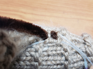 Close up of hooking the pipe cleaners thru a stitch. This keeps the pipe cleaners attached to the body.