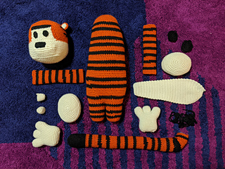 Large crochet tiger body parts laid flat on a purple and blue carpet; showing all the parts before joining.