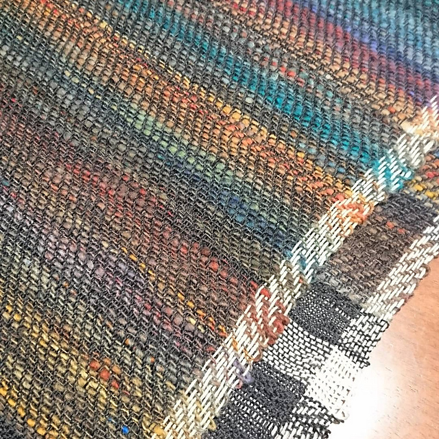 A folded piece of woven fabric with dark grey warp with white stripes along the selvedges. The weft is handspun singles in a thick & thin varied size, a shifting variety of colours (browns, reds, blues and greens).